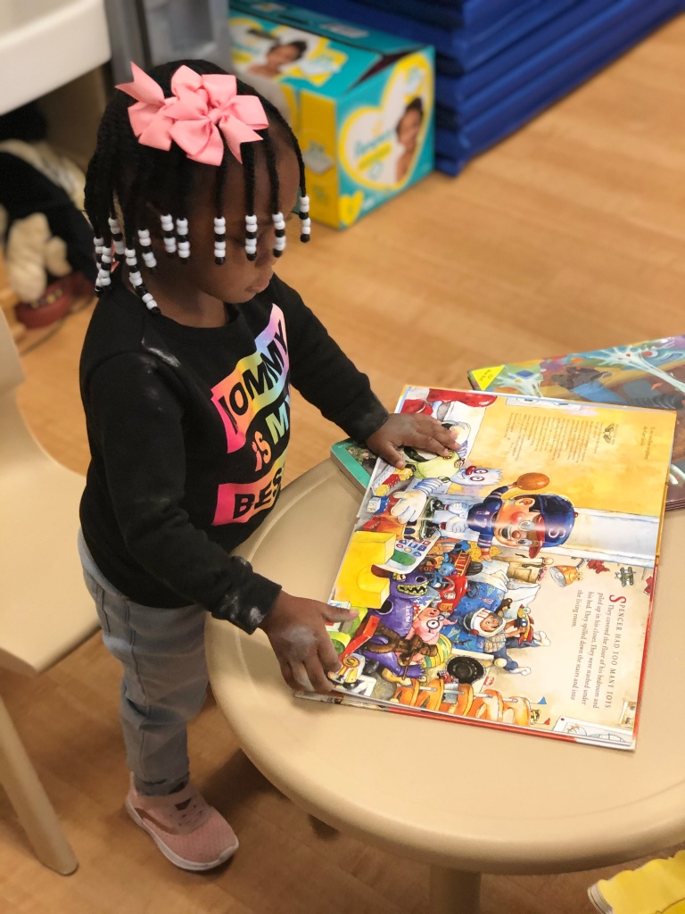A Pre-K student looks through a book in her classroom.