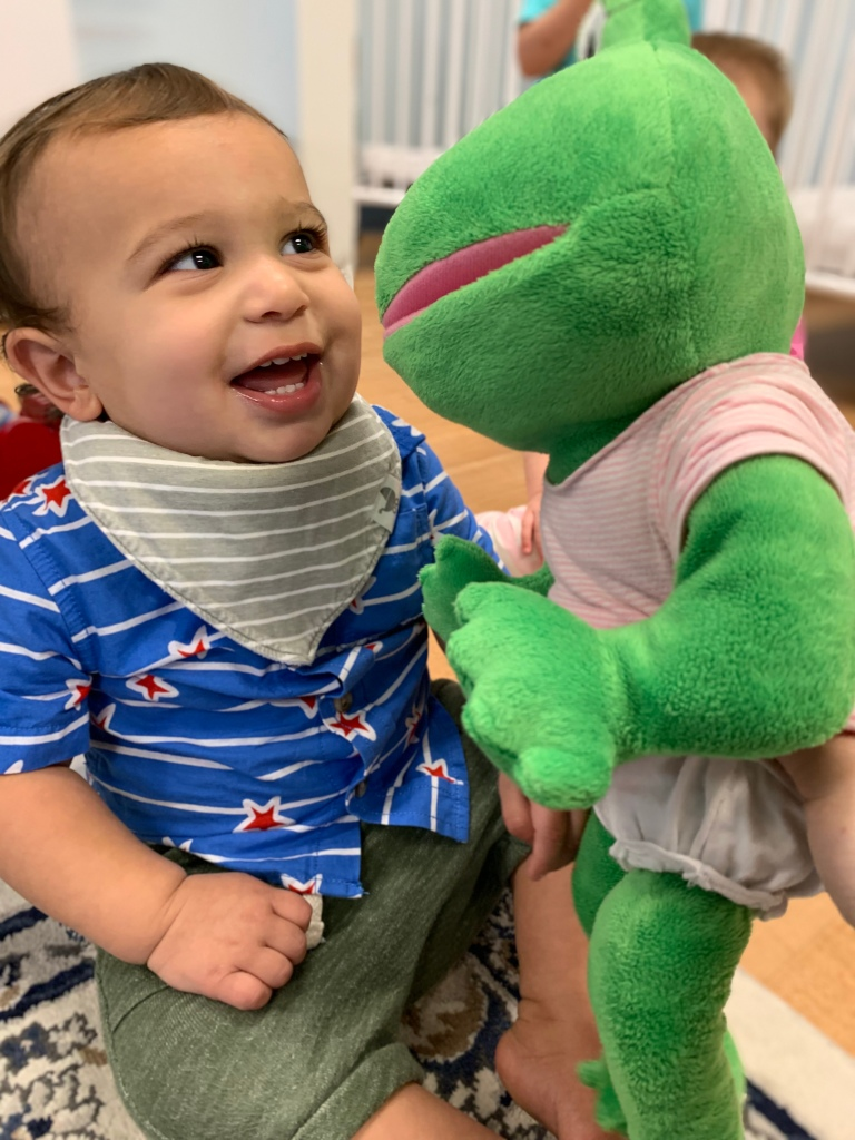 A young student smiles at a puppet.