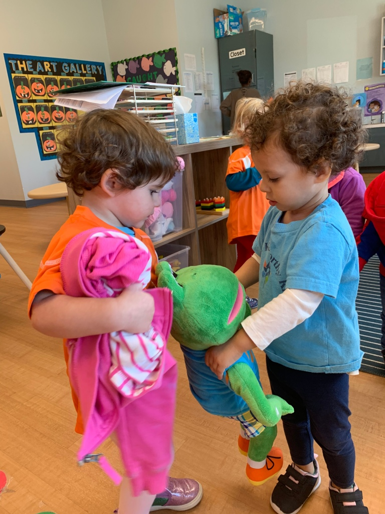 Two students share their toys in their classroom.