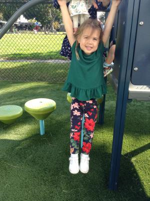 A Pre-K student swings on the playground and smiles for the camera.